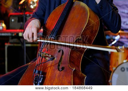 Man plays the cello on stage
