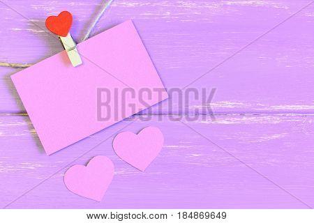 Clothespin hanging with pink blank paper card. Two pink paper hearts on wooden background with copy empty space for text. Wedding, Valentines day, birthday background