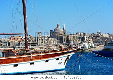 VALLETTA, MALTA - MARCH 30, 2017 - View of Valletta city buildings and waterfront seen from Sleima with yacht in the foreground Valletta Malta Europe, March 30, 2017.