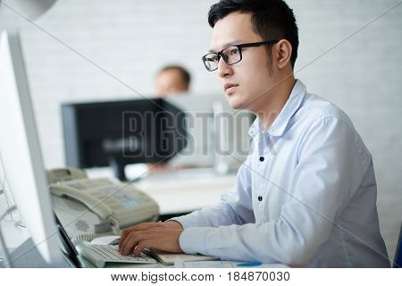 Young Vietnamese financial analyst working on computer in office