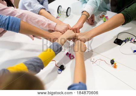 education, children, technology, science and people concept - group of happy kids with building kit making fist bump at robotics school