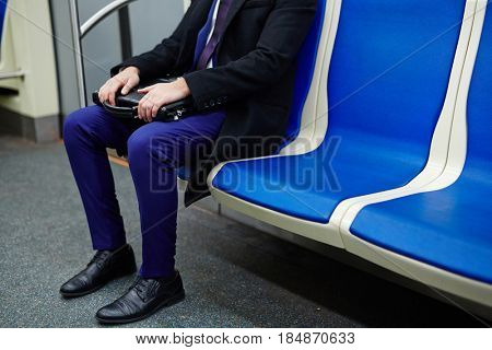 Low section portrait of unrecognizable man sitting in subway train, commuting to work