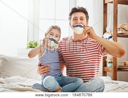 Happy father's day! Dad and his child daughter are playing and having fun together. Beautiful funny girl and daddy have mustaches on cups. Family holidays and togetherness.