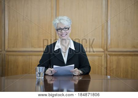 Caucasian businesswoman sitting in conference room with paperwork