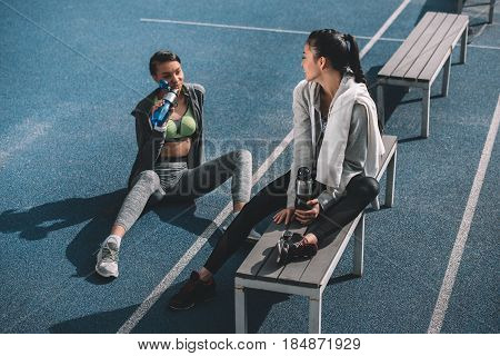 Smiling Young Sportswomen With Sports Bottles Resting On Running Track Stadium