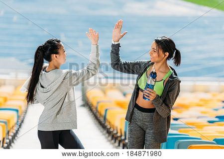 Two Young Sportswomen With Sport Bottle Giving Highfive On Stadium Stairs