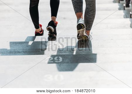 Low Section Of Two Young Sportswomen On Stadium Stairs