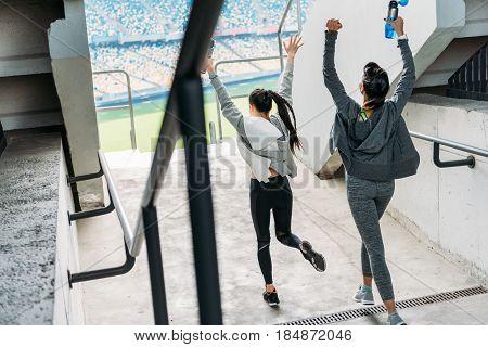 Rear View Of Two Happy Sportswomen In Sportswear Running To The Stadium