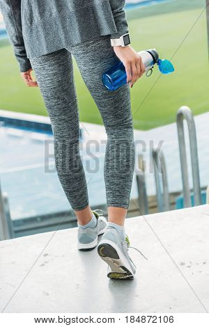 Low Section Of Young Sportswoman Holding Sport Bottle On Stadium