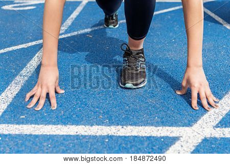 Close-up Partial View Of Sportswoman On Starting Line At Running Track Stadium