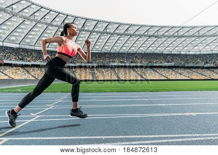 Side View Of Athletic Young Woman In Sportswear Sprinting On Running Track Stadium