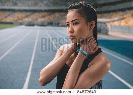 Young Asian Sportswoman Standing On Running Track Stadium And Looking Away