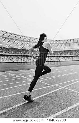 Young Fitness Woman In Sportswear Running On Running Track Stadium, Black And White Photo