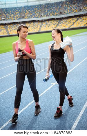 Tired Young Sportswomen With Bottles Of Water Walking On Running Track Stadium