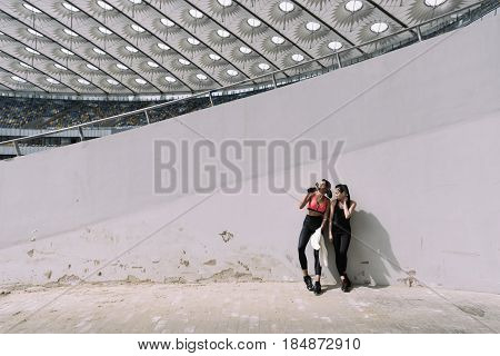 Two Young Sportswomen Resting On Stadium With Towel And Bottle Of Water
