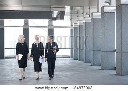Businesswomen walking together in office lobby