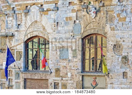 Windows, flags and a coat of arms on the facade of Palazzo Nuovo del Podesta in San Gimignano, Italy