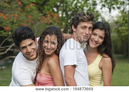 Hispanic couples hugging outdoors together