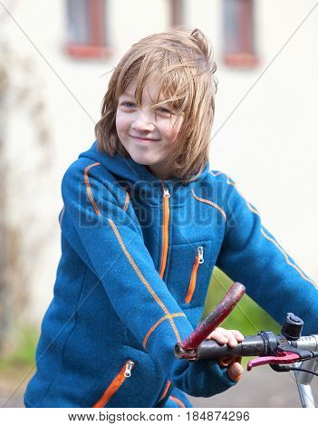 Portrait of a Boy on Bike with Blond Hair Smiling