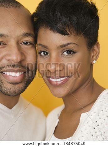 Black couple standing cheek to cheek