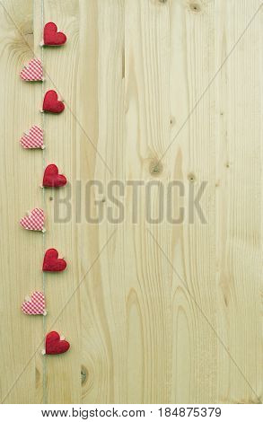 Nine hearts with clothes pegs on a cord on wood