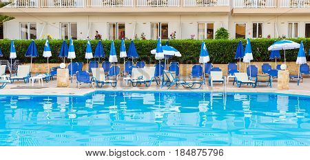 Relax and sunbathe by pool with clear blue water in Resort hotel. Empty pool without tourists early morning at hotel. Atali Village Bali Rethymno Crete Greece