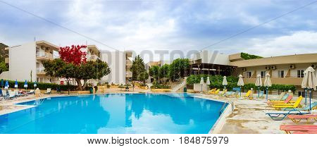 Bali Greece - May 2 2016: Empty pool without tourists at midday in hotel. Relax and sunbathe by pool with clear blue water in Resort hotel Atali Village 4 star. Bali Rethymno Crete Greece
