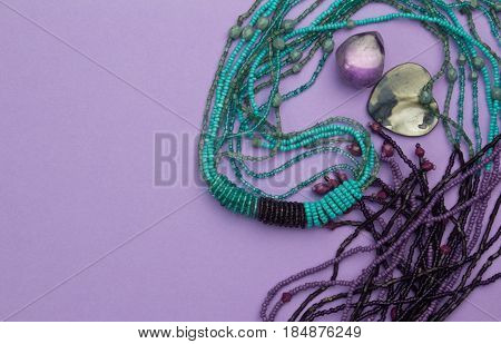 Purple background with beads mother of pearl heart pendant and amethyst gem stone