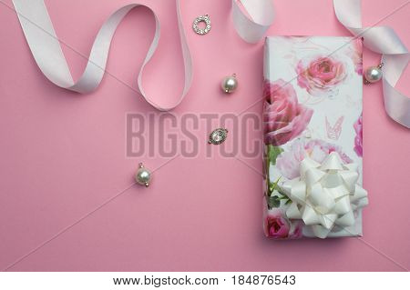 Mothers day pink background with wrapped gift white satin ribbon and pearl and crystal charms