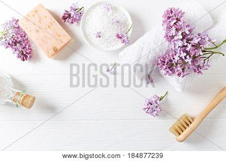 Natural bath salt, soap, cotton towels and lilac flowers (symbolic image)
