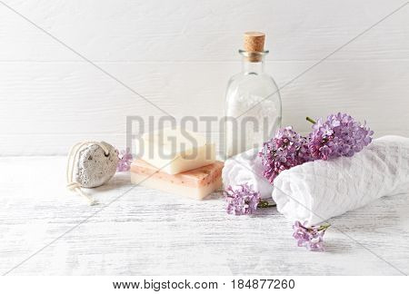 Natural bath salt, soap, cotton towels and lilac flowers (symbolic image)