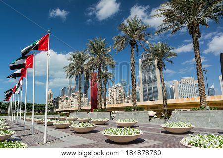 DUBAI, UNITED ARAB EMIRATES - DECEMBER 10, 2016: Dubai street near The Dubai Mall with palm trees and modern high-rise buildings. Modern architecture of Dubai, United Arab Emirates.