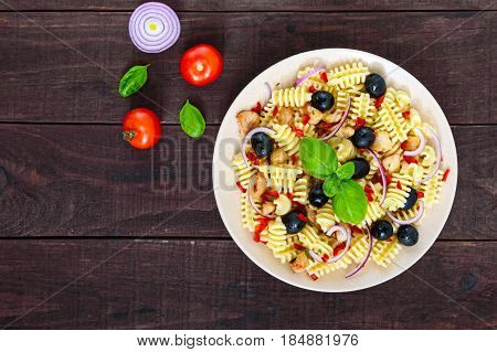 Pasta salad radiatori with chicken black olives blue onion sweet pepper on a dark wooden background. The top view.