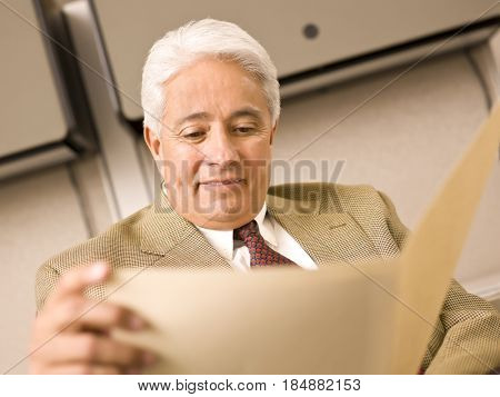 Hispanic businessman looking at folder