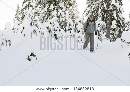 Caucasian woman snowshoeing in snow