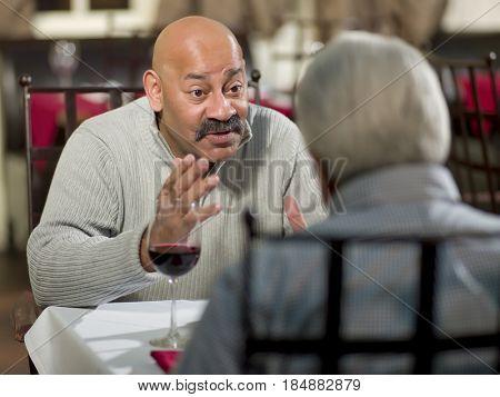 Hispanic men having dinner together in restaurant