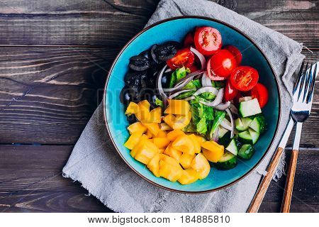 Greek salad with cucumber tomato yellow pepper olive onion and oil. Bowl of fresh summer vegetables salad on grunge wooden table background. Vegan vegetarian healthy dieting food concept.