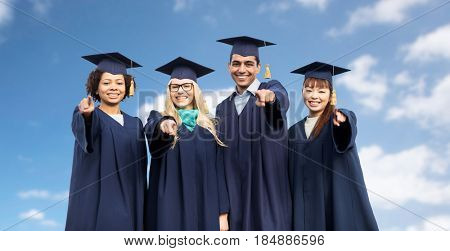 education, graduation and people concept - group of happy international students in mortar boards and bachelor gowns pointing finger at you over blue sky and clouds background