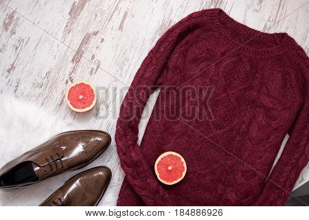 Maroon knitted sweater brown patent leather shoes cut grapefruit halves. Wooden background. Fashion concept. top view