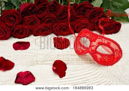 Red Carnival Mask On A Wooden Table On A Background Of Scarlet Roses