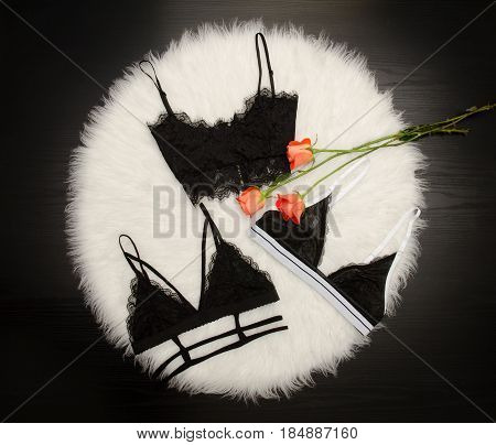 Fashionable Concept, Three Black Lace Bodices On White Fur, Orange Roses, Top View