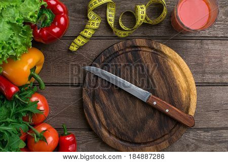 Sport and diet. Vegetables, a glass of tomato juice and centimeter. Peppers, tomatoes, salad on rustic background. Top view. Copy space