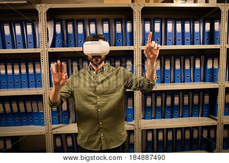 Businessman experiencing virtual reality in file storage room at workplace