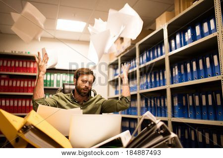 Irritated businessman throwing papers while sitting in file storage room
