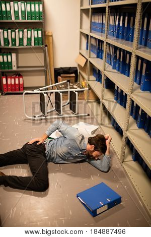 Fallen businessman with file in storage room at workplace