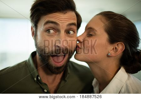 Close up of businesswoman kissing businessman in office
