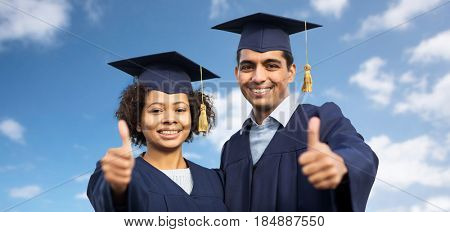 education, graduation, gesture and people concept - happy international students in mortar boards and bachelor gowns outdoors showing thumbs up over blue sky and clouds background