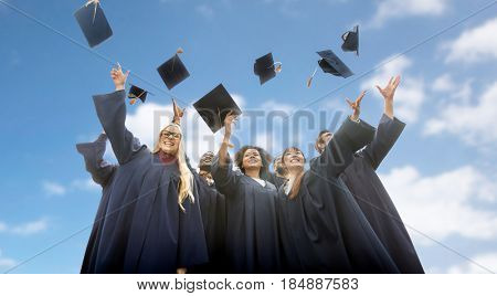 education, graduation and people concept - group of happy international students in bachelor gowns throwing mortar boards up over blue sky and clouds background