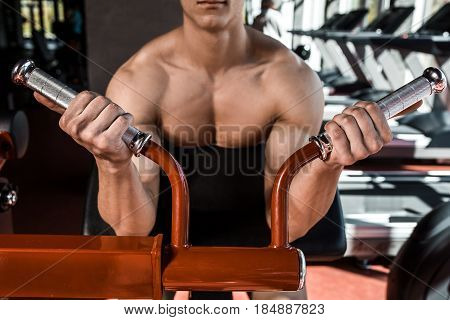 Muscular man doing exercises in the gym. Part of the body. Naked male torso. Close-up