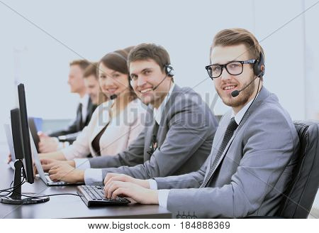 experienced assistants with a headset in front of computers in t